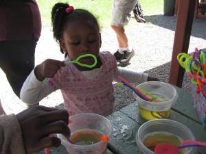 The STEM Mentor Program table and hands-on science experiment at the BBBS Summer Picnic.