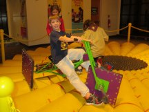 """Ride the square-wheeled tricycle in """"Pedal on the Petals"""" and experience a surprisingly smooth ride."""
